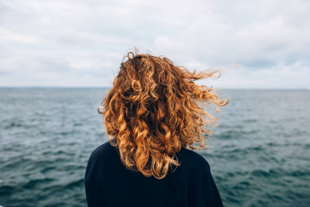 View from the back a woman with curly hair View from the back a woman with curly hair looks at the sea curly hair stock pictures, royalty-free photos & images