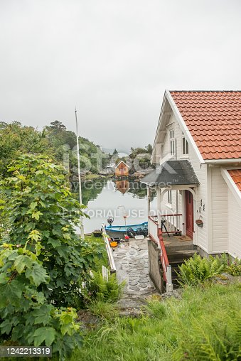 Lindesnes, Norway - June 27 2015: View from the back garden of a house over a small canal across to a small boat house..