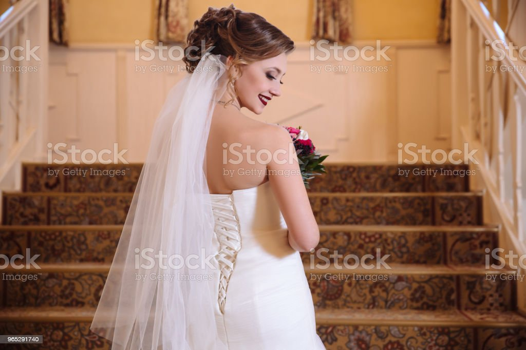 View from the back of a beautiful bride in a wedding dress with lacing rises the stairs, turning around and smiling. Face model rotated in profile zbiór zdjęć royalty-free