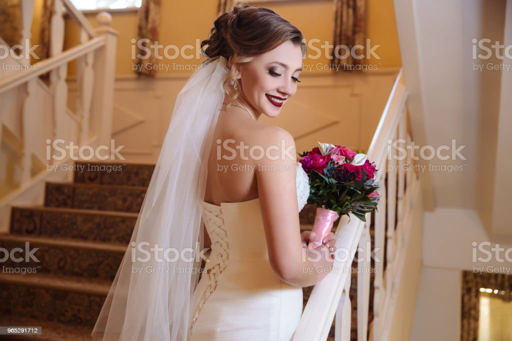 View from the back of a beautiful girl in white bridal wedding dress posing on stairs and laughing zbiór zdjęć royalty-free