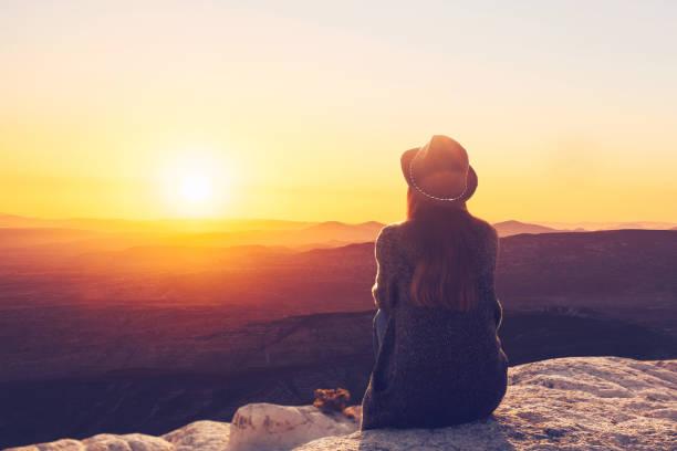 Ein Blick von der Rückseite eines Mädchens in einem Hut liegt auf einem Hügel und die schöne Aussicht bewundert. – Foto