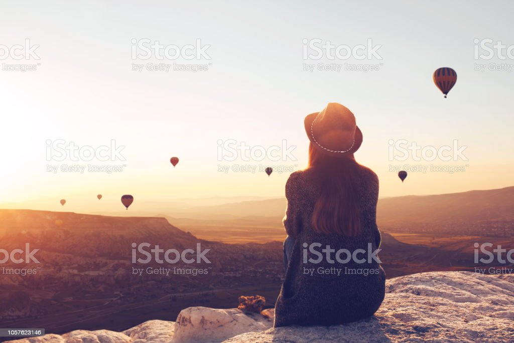Şapkalı bir kız arkası görünümünden bir tepe üzerinde oturur ve hava balonları görünüyor. - Royalty-free 13 - 19 Yaş arası Stok görsel