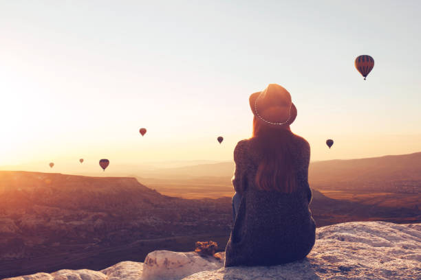 View from the back of a girl in a hat sits on a hill and looks at air balloons. View from the back of a girl in a hat sits on a hill and looks at air balloons in Cappadocia in Turkey. travel stock pictures, royalty-free photos & images