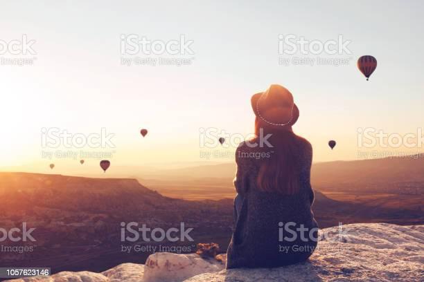 Uitzicht Vanaf De Achterkant Van Een Meisje In Een Hoed Ligt Op Een Heuvel En Kijkt Naar Lucht Ballonnen Stockfoto en meer beelden van Activiteit