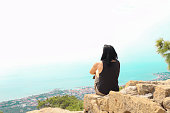 istock View from the back of a girl sits on a hill and looks at the sea 1284393086