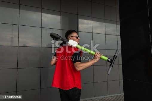 View from the back on an American young man with a hairstyle in a stylish red vest in sunglasses with an electric scooter in hands. Urban guy posing with a modern scooter in the city near a gray wall.