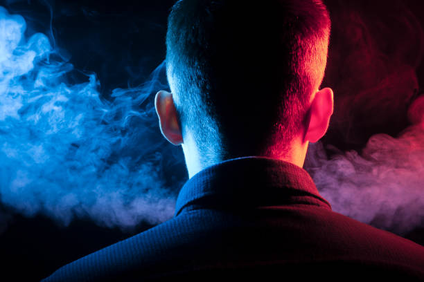 A view from the back on the head of a boy in a shirt smoking a vape and exhaling multi-colored smoke of blue and red at different directions from himself on a black isolated background A view from the back on the head of a boy in a shirt smoking a vape and exhaling multi-colored smoke of blue and red at different directions from himself on a black isolated background evaporation stock pictures, royalty-free photos & images