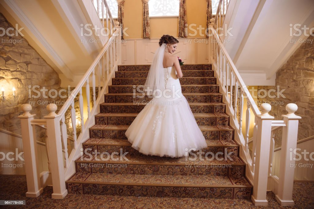 View from the back, the bride climbs the stairs in a beautiful tight dress, turns around and laughs royalty-free stock photo