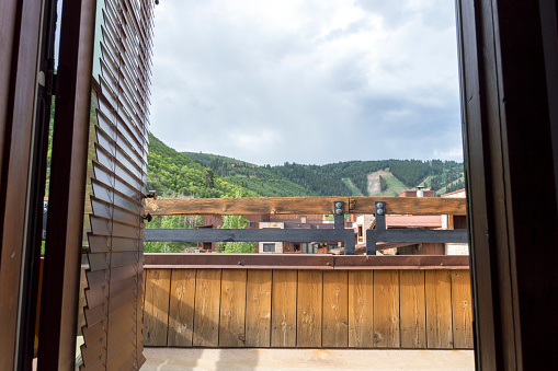 This shot was taken from the inside of a hotel room.  Visible in the shot is the room's balcony.  In the distance are surrounding mountains and a ski hill.  This shot was taken in the summer when the mountains are green and free of snow.