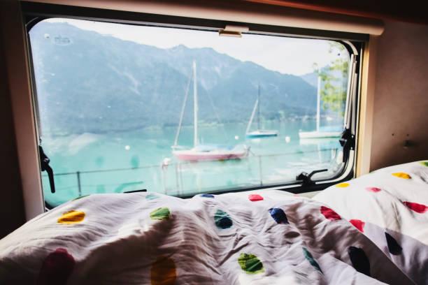 blick vom bett aus einem wohnwagen camping anhänger durch das fenster und ein see in der schweiz - nautisches schlafzimmer stock-fotos und bilder