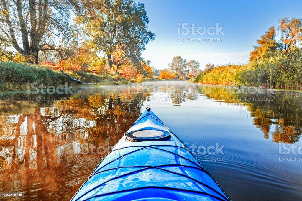Vista desde el kayak azul en las orillas del río amarillo otoñal deja árboles en otoño. El río Seversky Donets, otoño de kayak. Vista sobre nariz de kayak azul brillante. - foto de stock