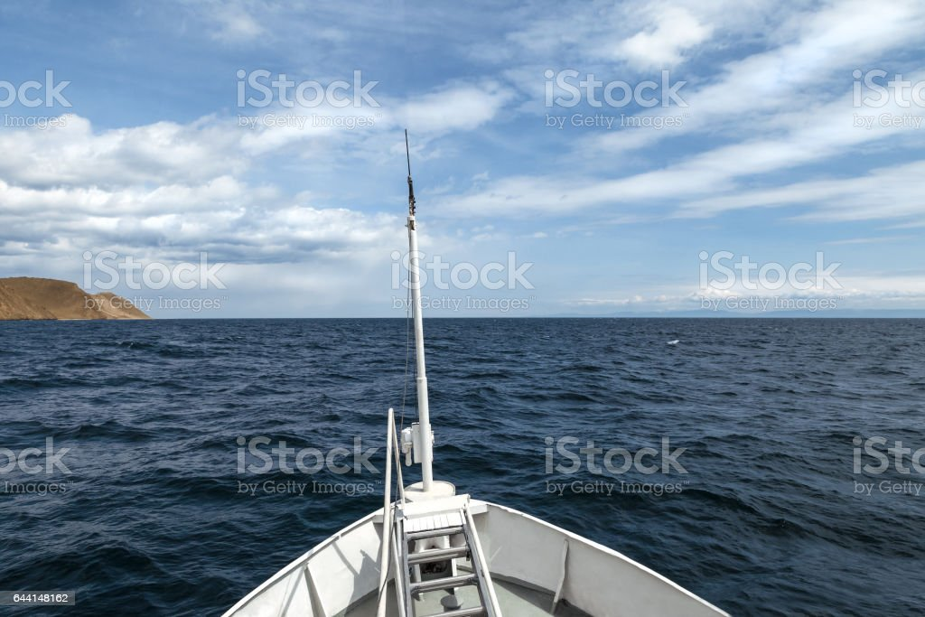 View from the bow of a ship on boundless water and beautiful clouds stock photo
