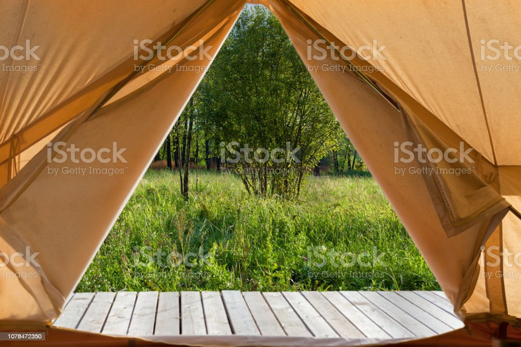 View from the canvas tent upon the green meadow - Royalty-free Artist's Canvas Stock Photo