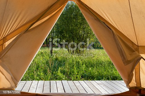 View from the canvas tent upon the green meadow with trees. POV