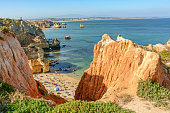 View from the cliffs to busy beach Praia do Camilo near Ponta da Piedade, Lagos Algarve Portugal