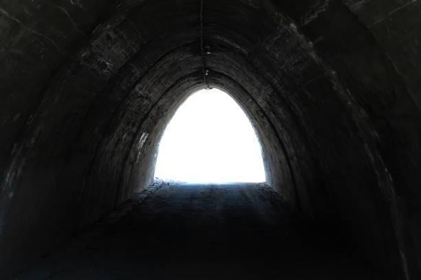 Vue du tunnel rugueux sombre sur le fond blanc isolé - Photo