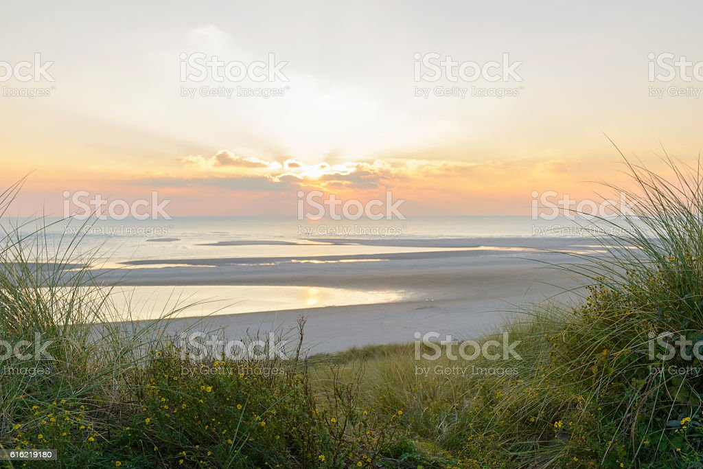 View from the dunes of a sunset at the beach stock photo