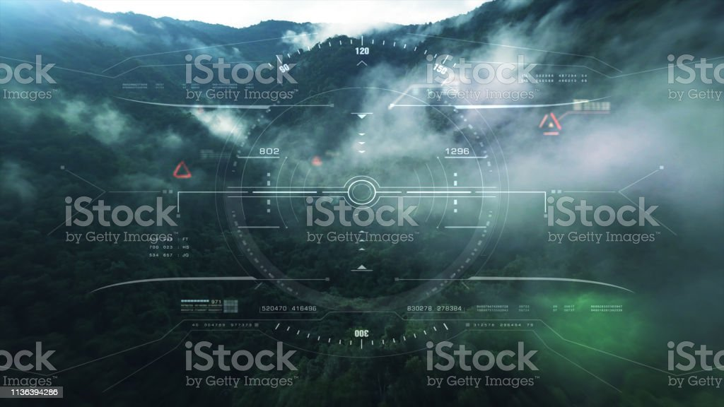 View from the fighter plane cockpit head up display Aerial view from the fighter plane's cockpit flying over the low cloud cover mountain scape with head up display acquire targets and enemies location hidden in the dense mountain forest Aerial View Stock Photo