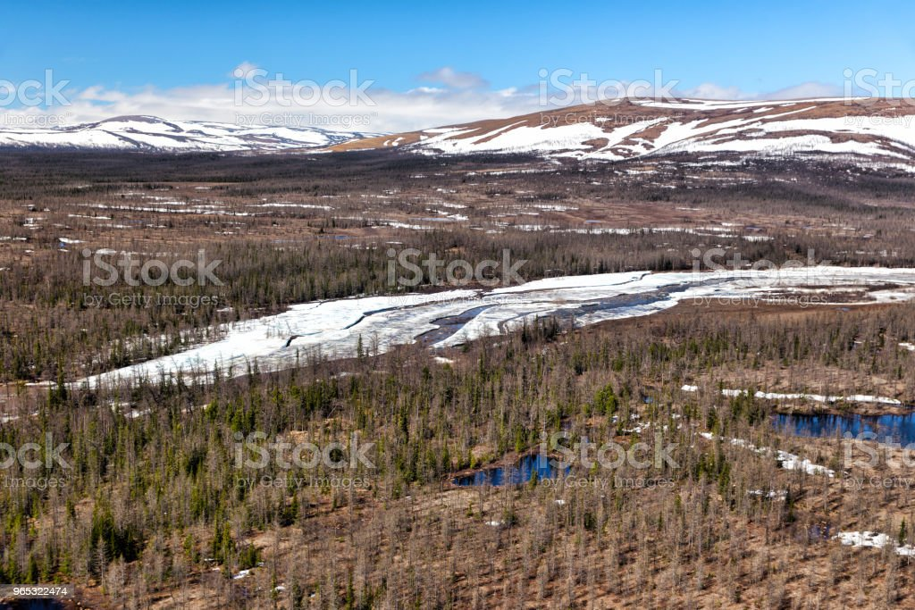 View from the helicopter to the valley of the mountain river. Northern landscape. The mountains are covered with glaciers royalty-free stock photo