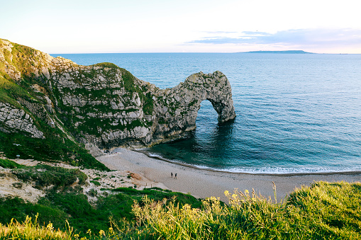 View from the hill over people walking on a beach by the sea and Durdle Door, UK