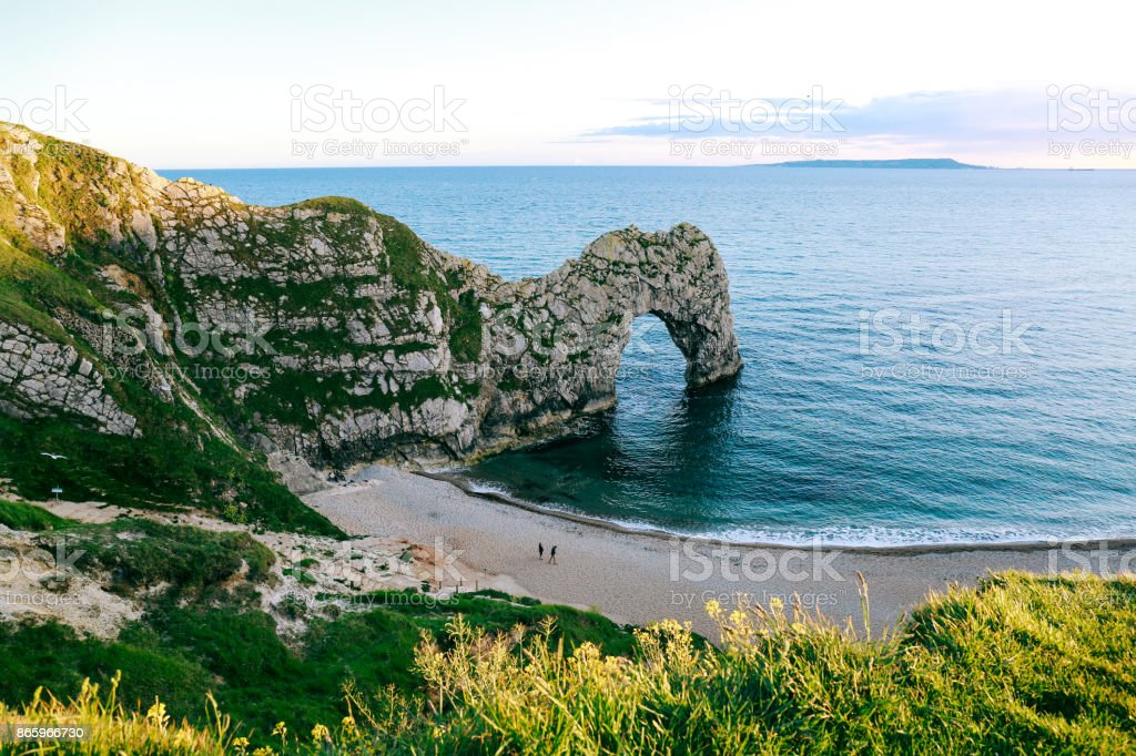 View from the hill over people walking on a beach by the sea and Durdle Door, UK stock photo