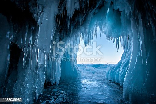 View from the ice cave on Lake Baikal. Many beautiful icicles on the walls and ceiling. Thick and thin icicles. Ice on the floor.