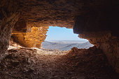 View from the inside of a cave to the rocky desert in the Sahara in Sudan lying under a glistening sun.