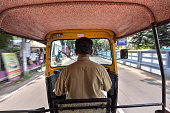 Kerala, India - May 08, 2018 : View from the inside of an auto-rickshaw, Indian TukTuk taxi running for passenger service on the road in Kerala, India. Tuk-Tuk is a motorcycle have a three-wheeler (Tricycle).
