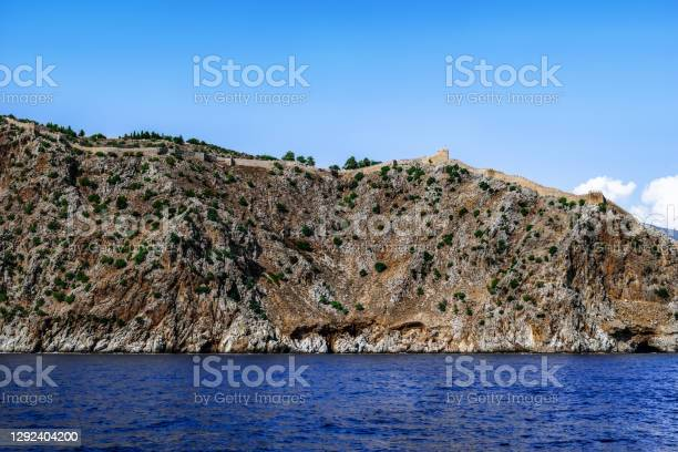 Photo of View from the Mediterranean Sea to the mountain with the ancient stone wall of the Alanya Castle on the peak (Turkey)
