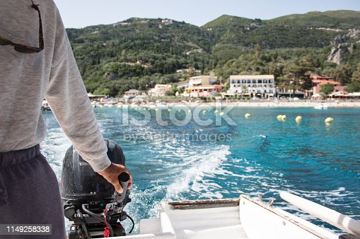 The hand of a man leads a boat on the sea. View from the motorboat to the waves of the azure sea, the beach, the resort and wooded cliffs. Sea voyage on the Ionic sea. Paleokastritsa. Corfu Island. Greece. Summer vacation. Relaxation Concept. Beaches of Greece