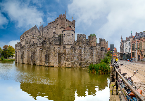 View from the river of the castle of Ghent in Belgium with blue sky and white clouds.