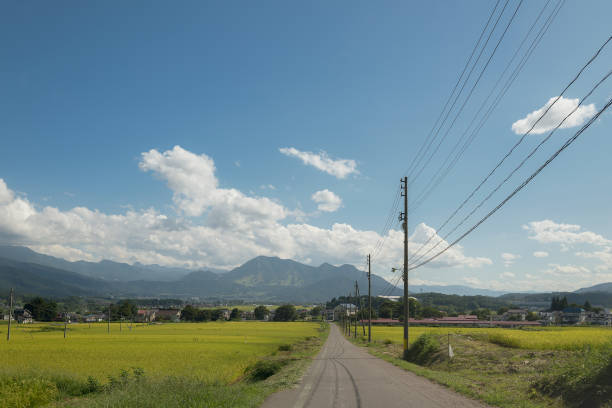 View from the road of Japanese Rice fields and mountains over the sky in Nagano. stock photo