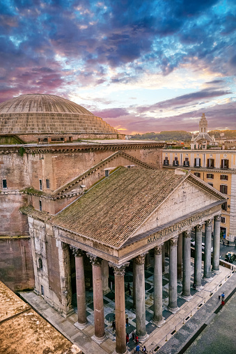 Rome, Italy -- A sunset view from the rooftops of the iconic Pantheon district in the heart of Rome. The famous Pantheon with its dome and colonnade is one of the best preserved Roman structures in the Eternal City. This temple was built in 27 BC. by the Consul Marco Vispanio Agrippa for the emperor Augustus and dedicated to all the Roman divinities. Currently the Pantheon is a Catholic church and inside there are the tombs of some members of the Italian royal family and the remains of the great Renaissance artist Raffaello Sanzio (Raffaello). Image in high definition format.