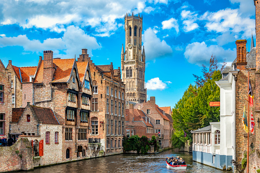 Belgium, Bruges - September 26, 2015: View from the Rozenhoedkaai in Bruges with the Perez de Malvenda house and Belfort van Bruges in the background and number of peoples in the boats.