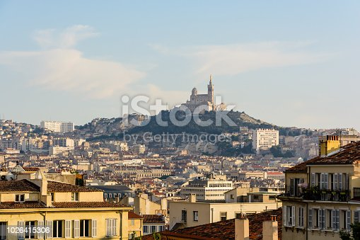 View from the Saint-Charles train station over the city of Marseille, France, at sunset with buildings in the foreground and the basilica of Notre-Dame de la Garde on top of the hill in the background
