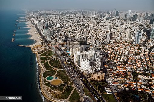 view from the shore to the modern district of Tel Aviv. Top view of the capital of Israel. Clean beautiful beach in the city center of the metropolis on the background of high skyscrapers.