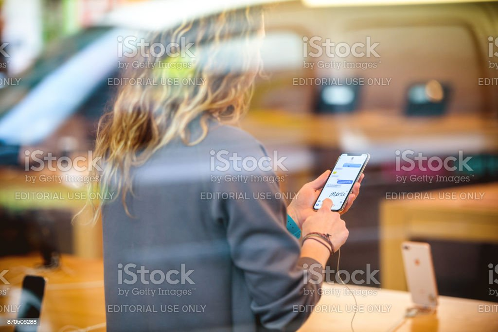 View from the street of Woman holding latest iPhone X inside Apple Store stock photo