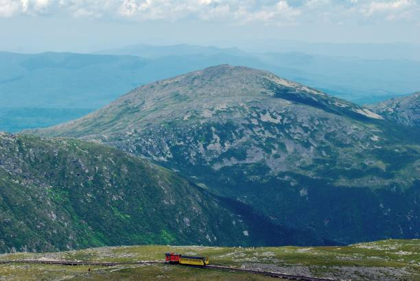 View from the top of Mount Washington View from the summit of Mount Washington on summer day with blue sky and train in the distance. mount washington new hampshire stock pictures, royalty-free photos & images