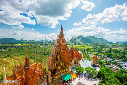 Above view of golden church with big buddha statue and rice field in Wat Tham Sua temple, Kanchanaburi, Thailand