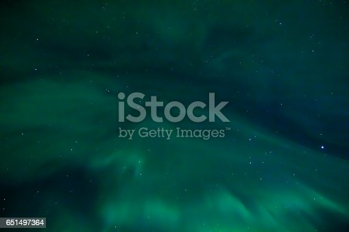 Photograph of the Icelandic night sky, with a bright green aruora borealis viewed from right under it. There are lots of stars shining too.
