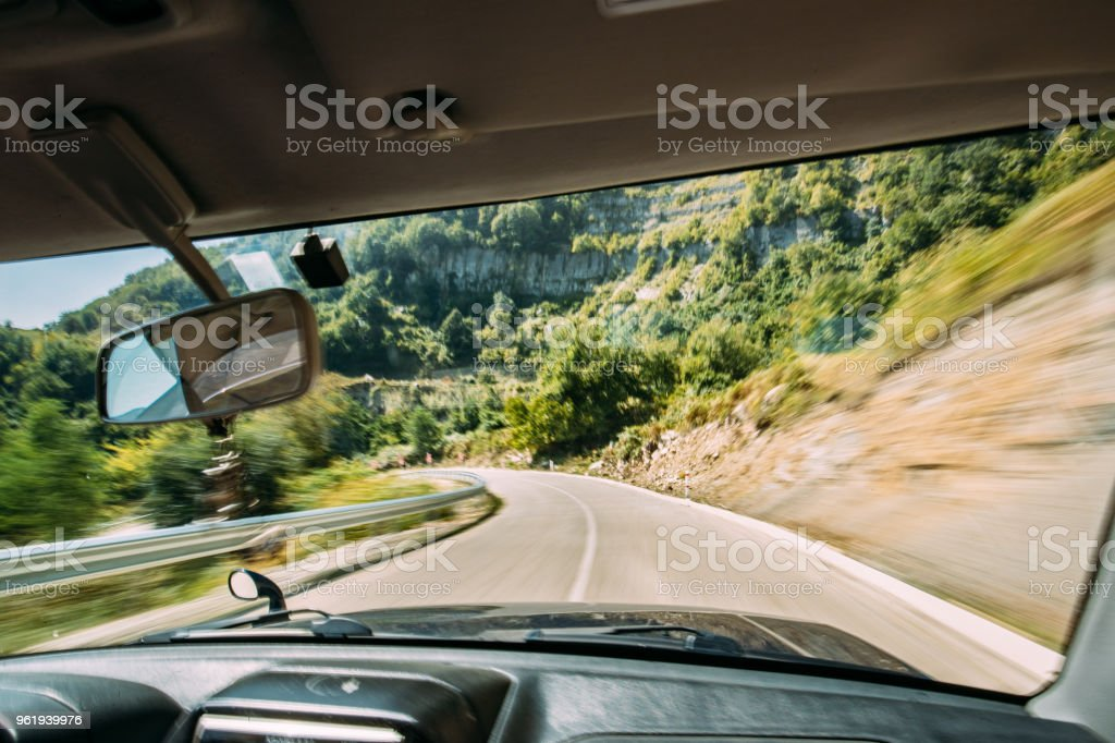 View From Vehicle Car Interior To Blurred Background Of Road In Fast Motion. Dangerous Fast Motion Movement In Route. Summer Asphalt On Mountain Road Motorway Highway. Travel Concept stock photo