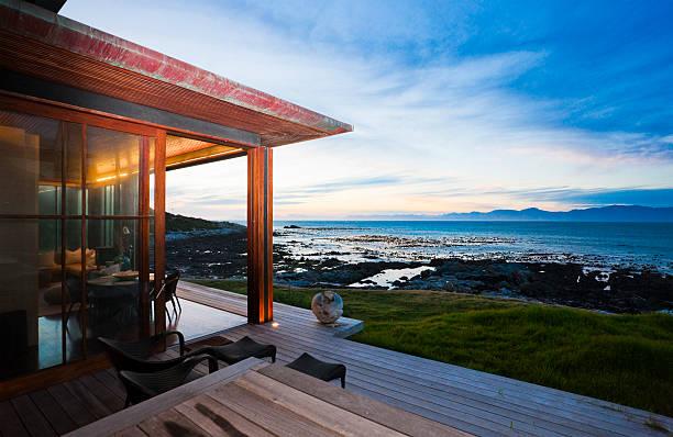 blick von der terrasse der strand-cottage über meer bei sonnenuntergang - cottage schlafzimmer stock-fotos und bilder