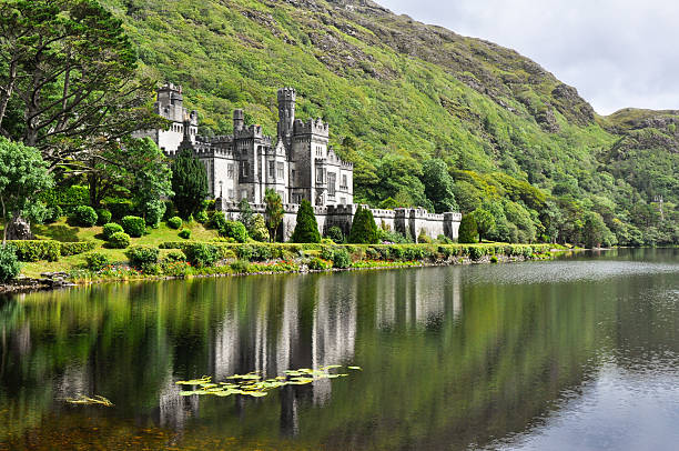 View from water of Kylemore Abbey near trees in Ireland stock photo