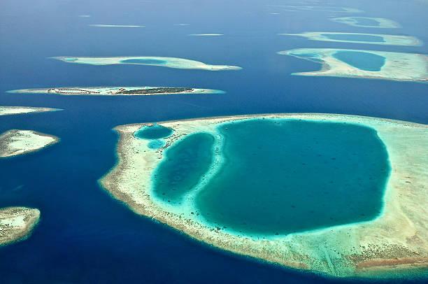 Vista dal waterplane alle Maldive island e le formazioni del reef atoll - foto stock