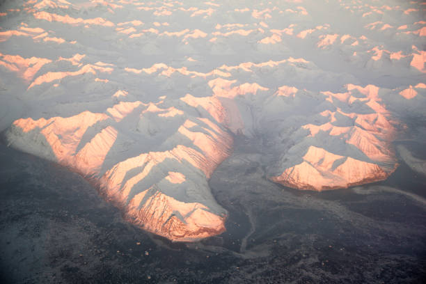 View frozen mountains from above with airplane during sunset, glaciers of Greenland stock photo