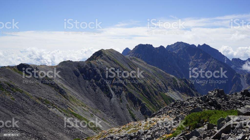 Una vista de Hodaka cadena de montañas de un camino encima de una montaña que conduce a la cima de una montaña en Nakadake - foto de stock