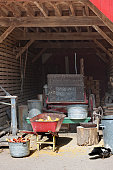A view through the doorway of an old storage barn, filled with old agricultural objects.