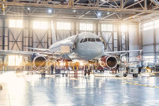 View inside the aviation hangar, the airplane mechanic working around the service