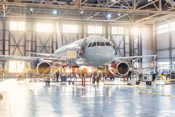uitzicht in de luchtvaart hangar, de vliegtuigmonteur werken rond de service. - luchtvaartindustrie stockfoto's en -beelden