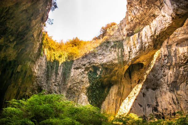 blick in die devetashka-höhle in der nähe des dorfes devetaki und des flusses osam in lovech, bulgarien. naturwunder. eine der größten karsthöhlen inosteuropas, in der heute fast 30000 fledermäuse leben - wasserfledermaus stock-fotos und bilder